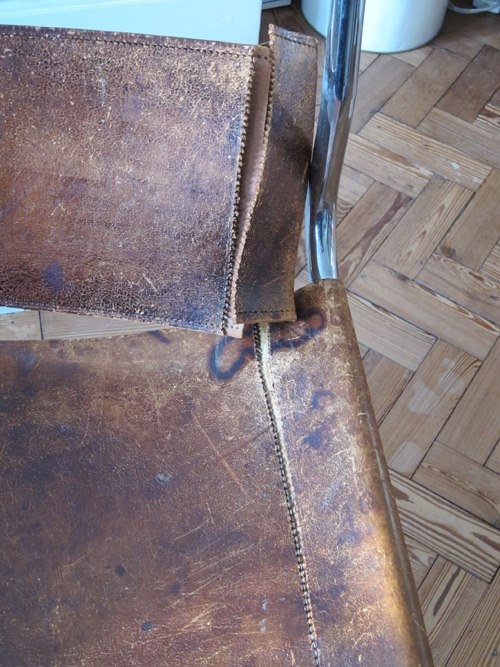 The stitching has given way and the leather is ripped, but the patina of the leather is great and it would be terrible to replace it.